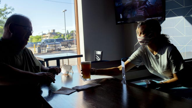 Bartender Mahgan Tomalia wears a mask while serving a beer to Flint resident Larry Furlette at The Eberson, which reopens fully for the first time amidst COVID-19 on Monday, June 8, 2020 in downtown Flint. Last week, the Michigan Department of Health and Human Services began reporting probable and confirmed cases of COVID-19, which increases the state's cumulative total.