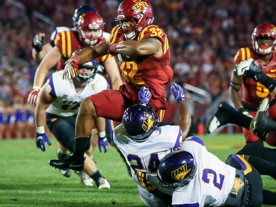 Iowa State running back David Montgomery (32) runs over Northern Iowa defensive back NikholiJaghai (24) and Malcolm Washington(2) during the first half Saturday, Sept. 2, 2017, at Jack Trice Stadium in Ames, Iowa.