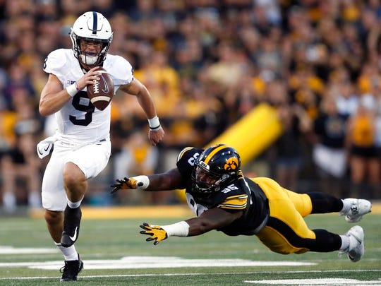 Penn State quarterback Trace McSorley (9) runs with the ball as Iowa defensive lineman Cedrick Lattimore defends during the first half of an NCAA college football game Saturday, Sept. 23, 2017, in Iowa City, Iowa. (AP Photo/Jeff Roberson)