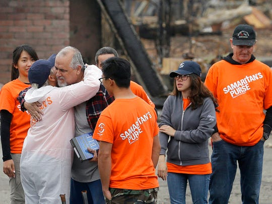 Larry Keyser, third from left, hugs volunteers from Samaritan's Purse disaster relief after they helped him sift through remains of his family's home destroyed by fires in the Coffey Park area of Santa Rosa, Calif., Wednesday, Nov. 8, 2017.