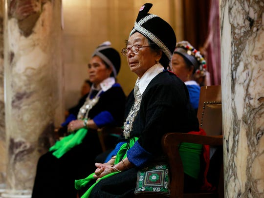 An elderly Hmong woman listens to a speech by Governor