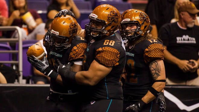 Rattlers wide receiver Maurice Purify (2) is congratulated by teammates for his touch down during the Arizona Rattlers and Pittsburgh Power arena football game at US Airways on Saturday, April 19, 2014 in Phoenix, Arizona.