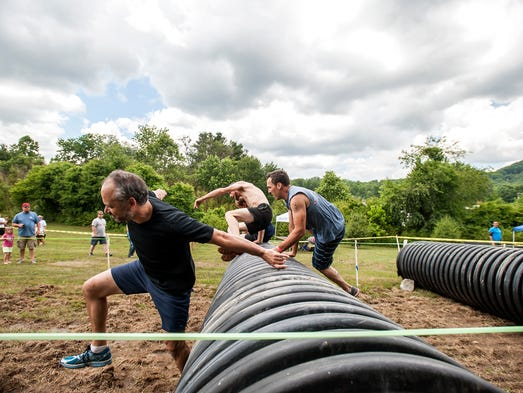 Racers hop over barrels for the first obstacle of the