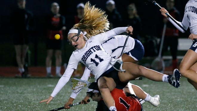 Brighton's Eleanor Burns tumbles to the turf after being upended by Penfield's Alyssa Sproule on March 29. Burns had two goals in the Barons' 12-6 win.