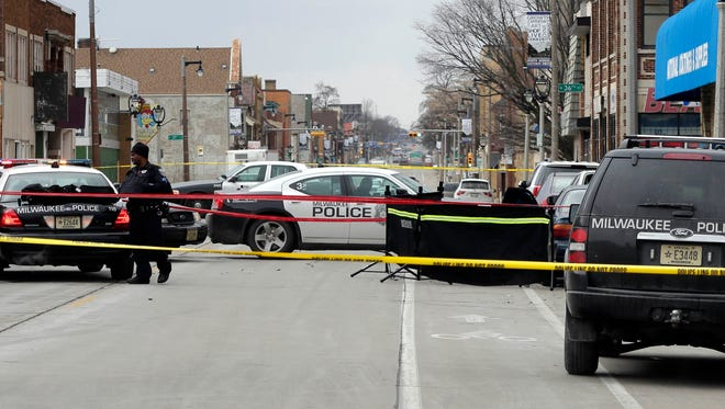 Police cars gather near a screen blocking an area in front of car with glass blown out of the windows where a man was fatally shot earlier Wednesday, near N. 35th St. and W. North Ave.