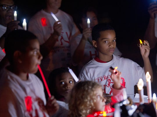 Alex Reid (right) participates in a the World AIDS Day candlelight vigil at Dreamland Park in Fort Pierce on Dec. 1, 2014. Danielle Baron, with the St. Lucie County HIV/AIDS Prevention Planning Group, said the event was a remembrance of those lost to the disease, a celebration of the progress made in its prevention and treatment, and an effort to fight the stigma of AIDS through education.