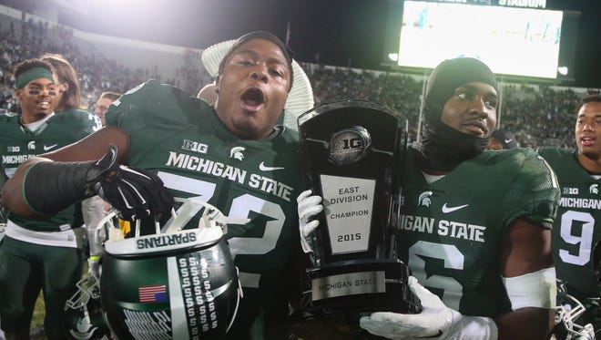 Michigan State's Craig Evans, left, and Aaron Burbridge celebrate with the Big Ten East Division championship trophy after beating Penn State, 55-16, on Saturday.