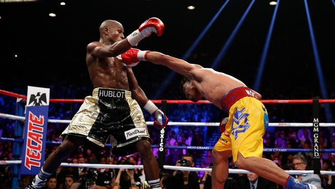 Manny Pacquiao, from the Philippines, right, hits Floyd Mayweather Jr., during their welterweight title fight on Saturday, May 2, 2015 in Las Vegas. (AP Photo/John Locher)