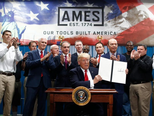 President Trump signs an executive order on the establishment of the Office of Trade and Manufacturing Policy at The Ames Companies in Harrisburg, Pa., in late April. The company's president, Robert Mehmel, looked over Trump's shoulder as he signed. He's a member of one of Trump's private golf clubs.