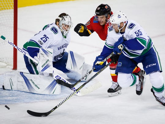 Vancouver Canucks goalie Jacob Markstrom, left, from Sweden, watches as Calgary Flames' Kris Versteeg chases the puck with Canucks' Alex Biega during the first period of an NHL hockey game Tuesday, Nov. 7, 2017, in Calgary, Alberta. (Jeff McIntosh/The Canadian Press via AP)