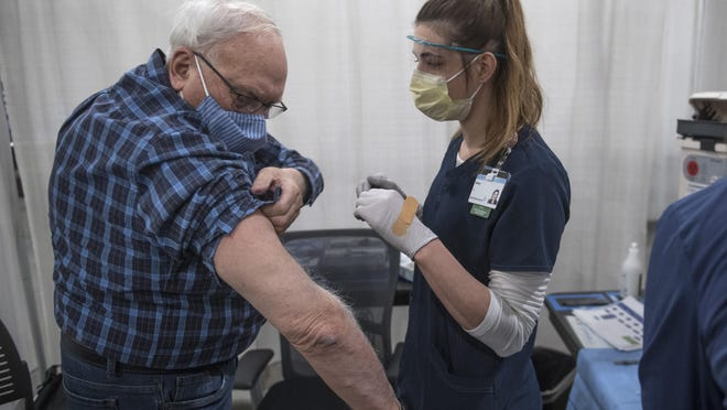 A health professional prepares to administer the first dose of a COVID-19 vaccine to a man at the West Michigan Vaccination Clinic at the DeVos Center in Grand Rapids, Mich. on Monday, Jan. 25, 2021. Health providers are directing requests to schedule a vaccine appointment to online sign-up sheets.