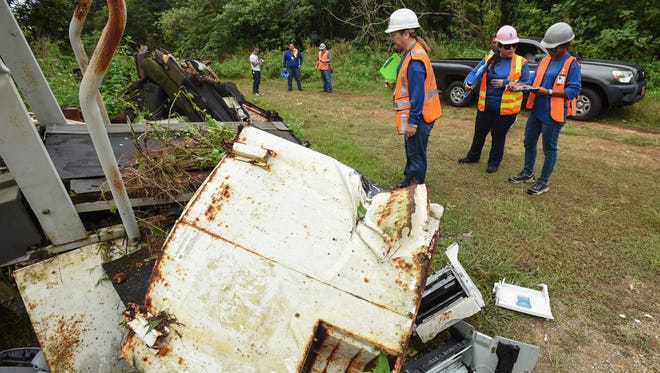 Guam Environmental Protection Agency employees, foreground, take notes on the types of illegally dumped trash that was being removed from the jungle near the Y-16 Guam Waterworks Authority water in Yigo on Friday, March 17, 2017.