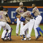 New York Mets teammates celebrate with Wilmer Flores, center, after he hit an 11th-inning, game-winning, walk-off RBI single in the Mets' 4-3 victory over the Toronto Blue Jays on Monday in New York.