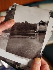 Buz Whiteley, who grew up on one of the Bangor homesteads, flips through photographs of his childhood home.