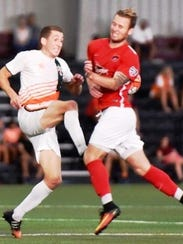 The Michigan Bucks' Tom Owens (left) converges with