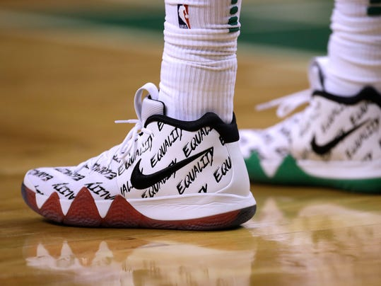 "FILE - In this Jan. 16, 2018, file photo, the word ""Equality"" adorns the athletic shoes worn by Boston Celtics guard Kyrie Irving during the second half of an NBA basketball game in Boston. Sneaker enthusiasts around the world eagerly await NBA All-Star weekend when new and limited editions of the latest shoes make their debut, but the month leading up to highly anticipated shoe palooza is a time often used to make a social statement.(AP Photo/Charles Krupa, File)"