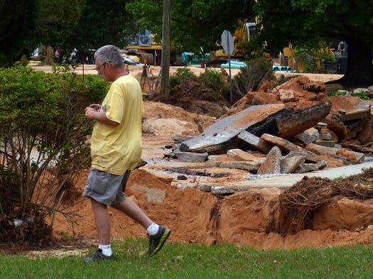 Tom McKean walks past a section of Piedmont Road near the Summit Boulevard intersection in the Cordova Park subdivision.  This part of Cordova Park, and Piedmont Road in particular, was badly damaged by flood waters caused by heavy rains moving through the Pensacola area last week.