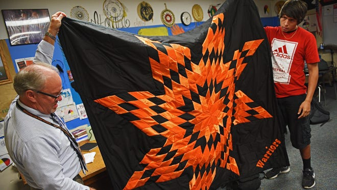 Washington High School teacher Bruce Rekstad and student Deion Larsen hold up a star quilt that will be presented to South Dakota State University President Barry Dunn at his inauguration on Thursday, Sept. 29, 2016, during a Native American Studies class at Washington High School Wednesday, Sept. 28, 2016, in Sioux Falls.