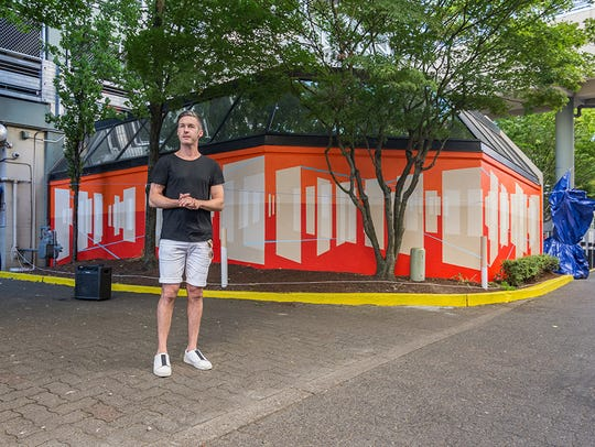 Damien Gilley stands outside his 3D mural that covers
