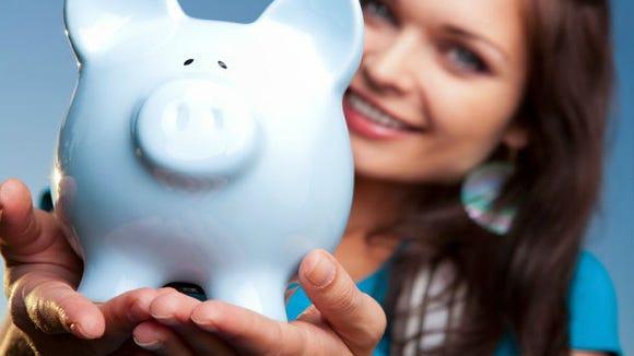 Woman holds piggy bank