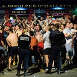 Police stand guard as England fans gather and chant slogans in the port area of Marseille, late on June 9, 2016, ahead of the start of the Euro 2016 football tournament in France.