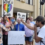 Edgar Orea, right, preaches Thursday to a group of same-sex marriage supporters who gathered outside the Carl D. Perkins Federal Building in Ashland, Kentucky. Hundreds gathered awaiting the arrival of Rowan County Clerk Kim Davis who has been ordered to appear in federal court to explain why she is refusing to issue marriage licenses despite a federal order to do so.