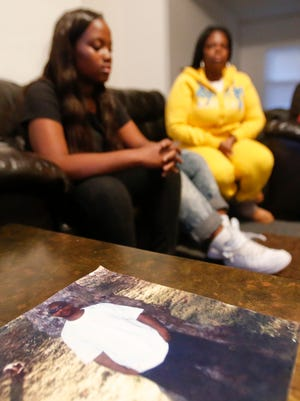A photo of Jerome Green rests in front of Enfinity Green, 16, one of his daughters, and her mother, Rosalynn Webb, at their Wilmington home on Oct. 15, 2015. Rydell Mills was charged with first-degree murder last year in the shooting death of Green, but a judge has granted a motion to suppress two statements he gave.