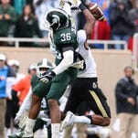 MSU cornerback Arjen Colquhoun knocks a fourth down pass away from Purdue receiver Gregory Phillips at the end of the game to preserve MSU's tight 24-21 victory at Spartan Stadium Saturday.