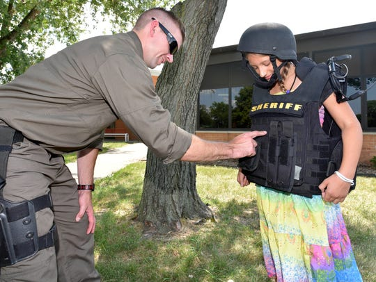 SWAT officer Chris Bennett talks to Camp Care attendee Madeline, explaining that his vest weighs so much because of the armor plates inside.
