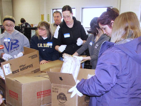Volunteers pack donated items for the Food Bank of