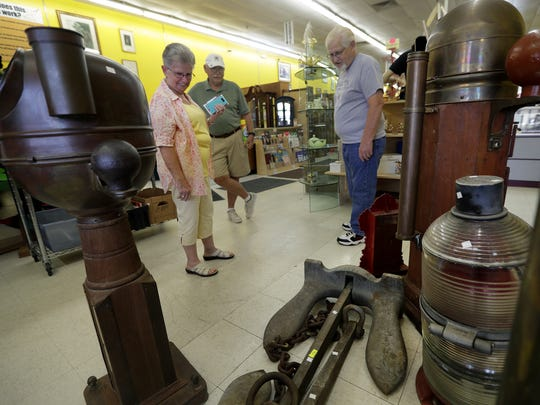 Leslie, Tom and Paul Vanden Boogaard discuss an antique anchor for sale at BumblePuppy Estate Sales in Grand Chute.