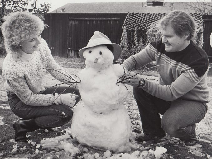 Mark and Mary Nord kneel next to a snowman they built