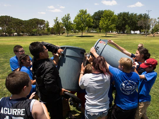 Campers at the Las Cruces Police Departments Youth Leadership Camp, take two large trash cans filled with water and dump them on each other during a large water balloon fight Thursday June 7, 2018 at Young Park. The water balloon fight was held on the penultimate day of the week-long camp.