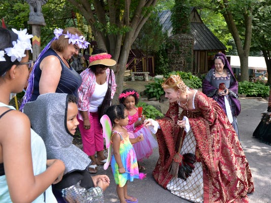 "Queen Catherine of Aragon, portrayed by Kristen Spangenberg, visits with children to give them a gift with ""sparkle and shine"" at the PA Renaissance Faire on Saturday."
