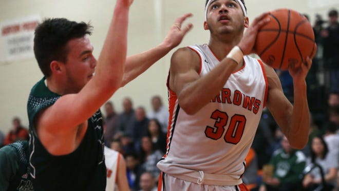 Ashland's Manny Langston pushes against Madison's Nick Smith while going for the hoop during a home game on Friday.