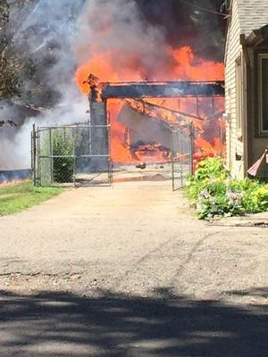 Neighbors heard a couple of loud noises just before a garage in the 3400 block of Lakeview Drive went up in flames in Highland Township early Monday afternoon.