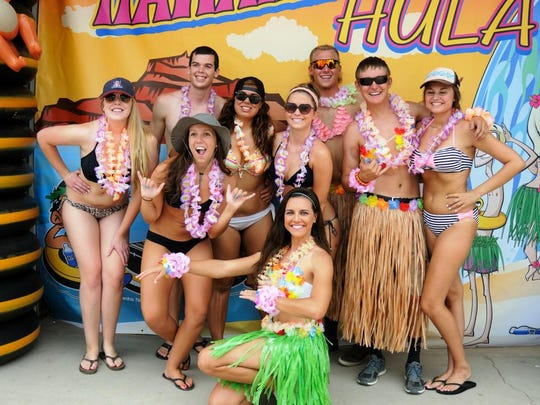 People celebrate with leis and grass skirts during Salt River Tubing's Hawaiian Mega Hula event.