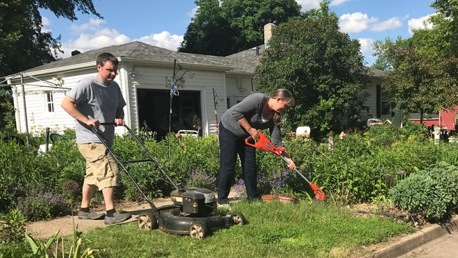 Ryan Hall mows while Councilor Theresa Stehly uses a string trimmer to clip the grass around the shrubs and flowers at her Van Eps Avenue home Tuesday afternoon after receiving notice from the city her yard was in violation of city ordinance.