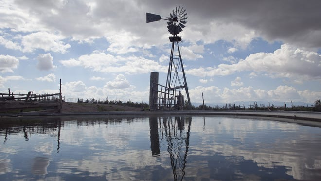 A windmill pumps water for ranchers north of Enoch.