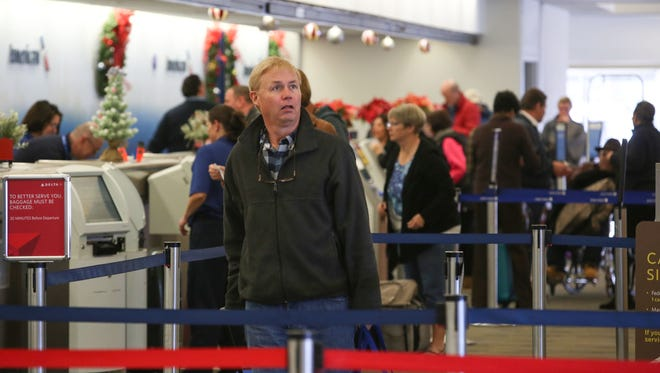 An airline passenger looks to see what gate he's flying out of after checking in at the Palm Springs International Airport, December 19, 2016.