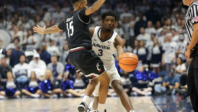 Xavier Musketeers guard Quentin Goodin (3) passes ball up-court as Cincinnati Bearcats guard Cane Broome (15) defends in the second half of the 85th Crosstown Shootout college basketball game between the Cincinnati Bearcats and the Xavier Musketeers, Saturday, Dec. 2, 2017, at Cintas Center in Cincinnati.