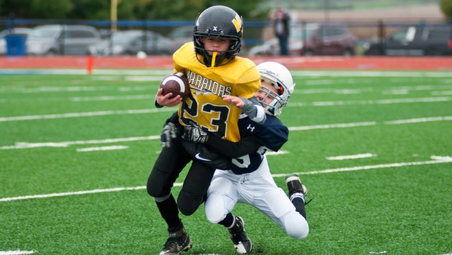 Brayen Hart carries the ball Sunday during Watkins Memorial Gold's 38-0 victory against Granville Navy in the Licking County League Youth Football Jerry Miller Championship game at Lakewood High School.