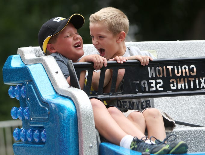 AJ Johnson, 7, and Ben Houston, 8, of Amelia, laugh as they ride the Sizzler during the New Richmond River Days festival on Sunday, August 17.