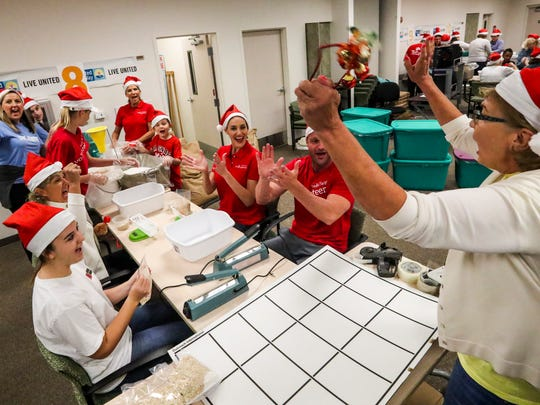 A team cheers after filling a box. These will be distributed to United Way houses and other partnering agencies that help people who are still recovering financially from Hurricane Irma.