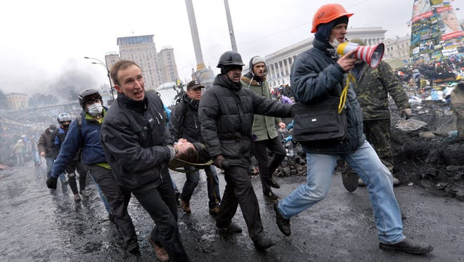 Anti-government protesters carry a fellow protester who was wounded during clashes with riot police in central Kiev on Feb. 20.
