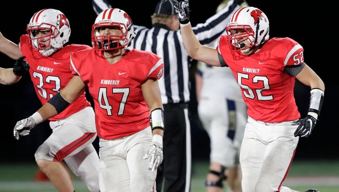 Kimberly's Alex Hammen (33), Tristan Argall (47) and Tyler Wright (52) celebrate their 38-31 victory against Appleton North last season.