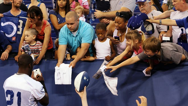 Cornerback Vontae Davis (21) signs autographs for members of the audience before public practice at the annual Indianapolis Colts mini-camp and fan open house at Lucas Oil Stadium in Indianapolis, Ind., Wednesday, June 10, 2015.