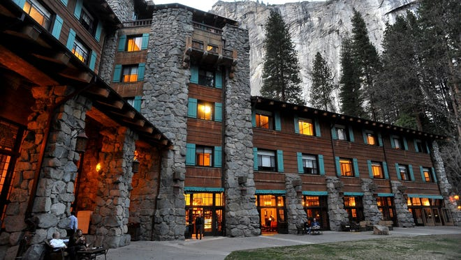 File - In this March 24, 2014 file photo, the historic Ahwahnee Hotel is lit up as dusk falls over Yosemite National Park, Calif. A new concessionaire takes over Tuesday at the park and many of the landmark places will have name changes at least temporarily because the old concessionaire lays claim to the names. The famed Ahwahnee Hotel is set to become the Majestic Yosemite Hotel.