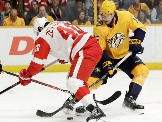 Detroit Red Wings center Henrik Zetterberg (40), of Sweden, and Nashville Predators right wing Craig Smith (15) battle for the puck in the third period of an NHL hockey game Saturday, Feb. 17, 2018, in Nashville, Tenn. (AP Photo/Mark Humphrey)