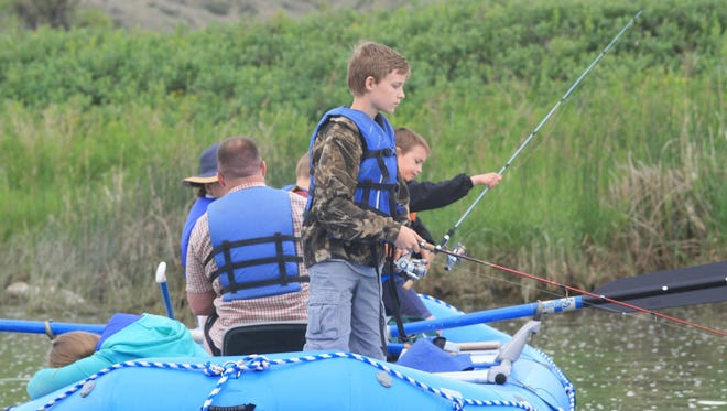 Lane Gibney fishes in foreground while Jack Gibney prepares his fishing pole in the background during a float from Carter Ferry to Fort Benton.